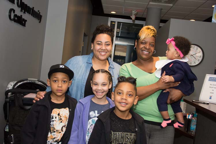 Stephenie Potter with her children, Robert, Kamariona, and RahMya and baby Reighlyn held by Taneka Thomas, Workforce Development Liaison. Photo by Susan Andress