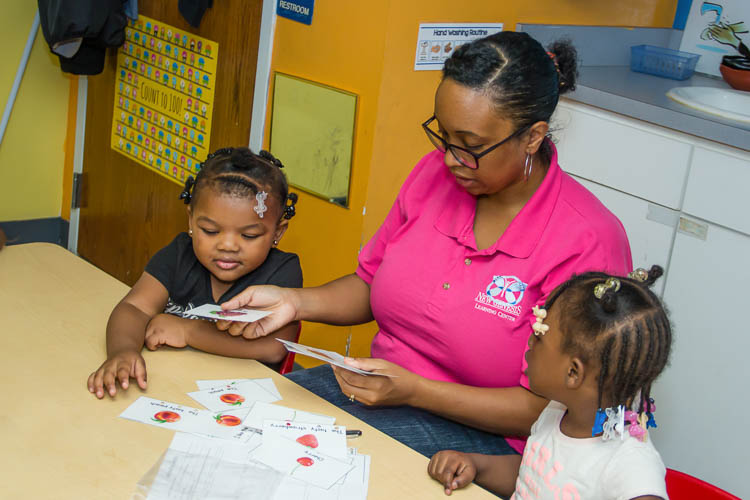 Preschoolers and Mrs. Karmin Armstrong-Andrews work together on learning at New Genesis.