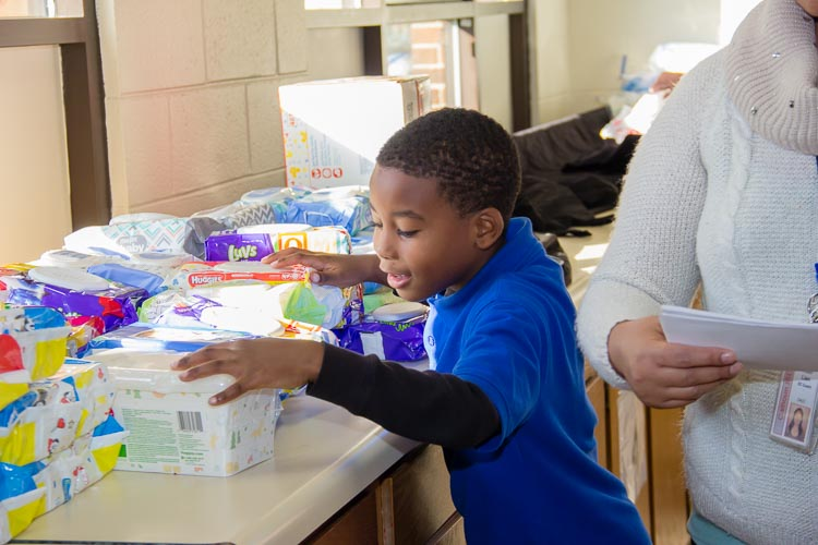 Joseph hands out sanitary wipes at recent diaper distribution. He was working toward a merit badge.
