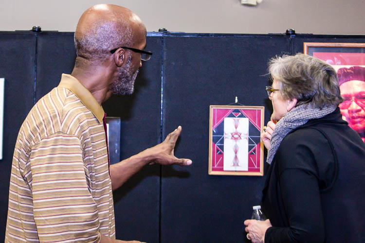 Thomas Woodruff, featured artist at the Northside Art Hop, discusses his work with patrons.