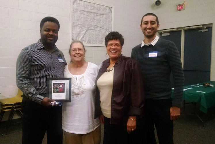 Jermaine Jackson, Brenda Hughes, Judi Rambow and Fernando Ospina of the Kalamazoo Public Library's Antiracism Transformation Team accept an award from ERACCE.