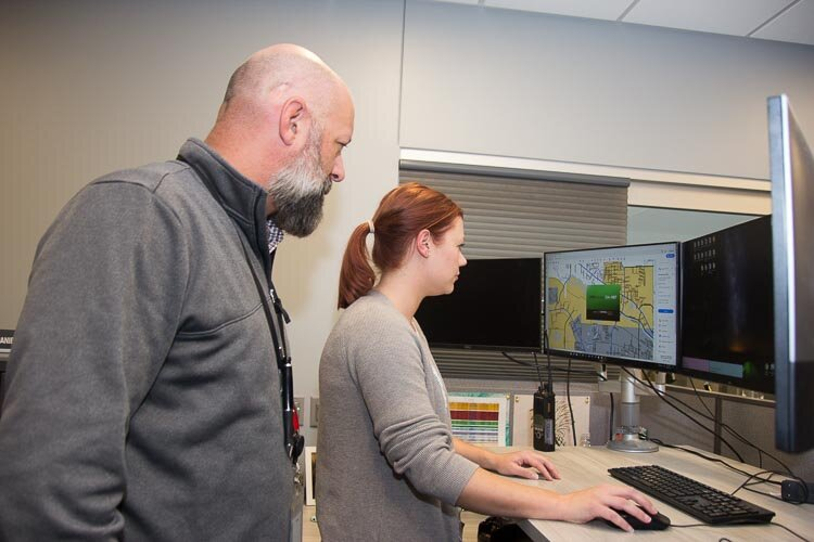Kevin Kellums and Whitney Perigo, crime analyst, at work at the Fusion Center.
