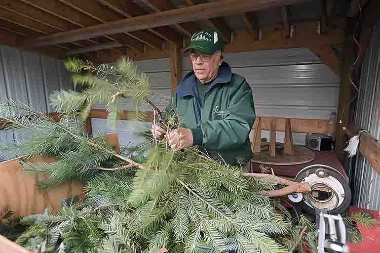 Ed Carpenter makes wreaths from excess boughs in their wreath making shop. Photo by David Trumpie