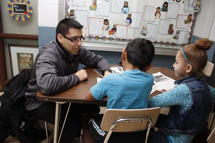 Israel Flores with reading buddies Tori and Joel  Photo by Susan Andress