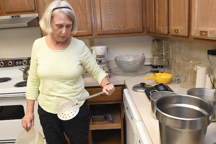 Janet Chichester sorts through kitchen equipment at the Trinity Neighborhood Center