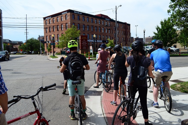 Crossing Kalamazoo Avenue on Pitcher Street: Where should a cyclist wait for the light to change? On the road, or on the sidewalk?