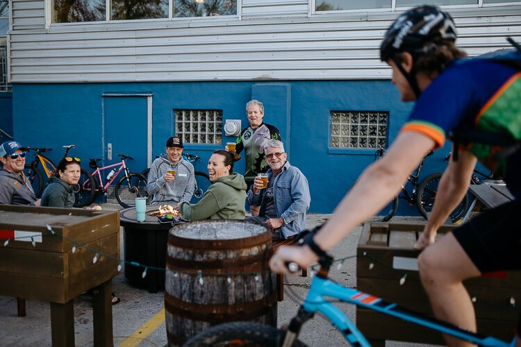 Members of the cycling group Spoke Junkies gather outside River's Edge Brewing Company in Milford after their bi-weekly ride.