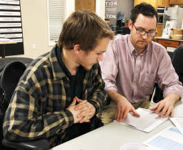 Quentin Bishop helps a student with his business plan.