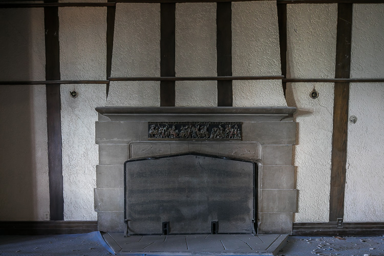 A decorative fireplace awaits its restoration.