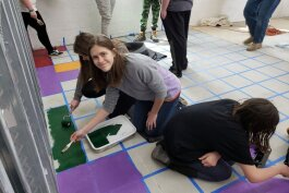Teens paint the floor of the River Rec Teen Zone in Marine City.