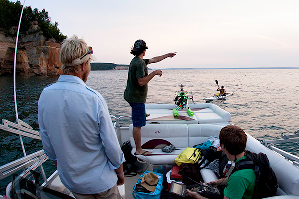 Clear & Cold Cinema member Dan Englund, pointing, directs kayakers during aerial filming on Lake Superior