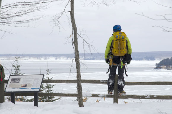 An ice climber takes in the views on Grand Island.