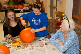 Big Brothers Big Sisters participants carve pumpkins at Eastwood Nursing Home in Negaunee.